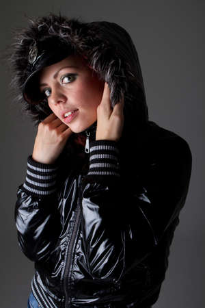 Young fashion model over dark background. She is wearing warm outfit. Very sexy. photo