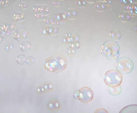 Blow Bubbles over a studio background. Lots of them. photo