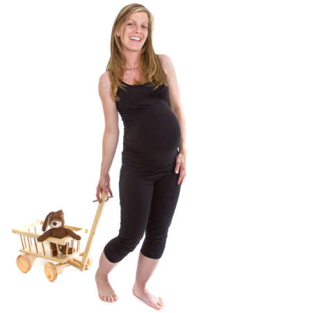 Young fresh pregnant woman is pulling  a trolley filled with toy animals isolated over white background. Stock Photo - 7291870