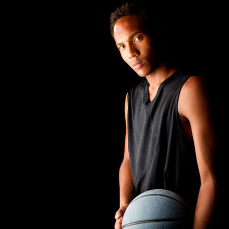 teens playing: Young black basketball player over black background. Young, fresh and stylish