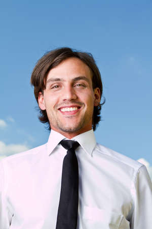 Young businessman with longer hair over a blue sky outside. Stock Photo - 7336439