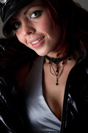 brown leather hat: Young fashion model over dark background. She is wearing warm outfit. Very sexy. Stock Photo
