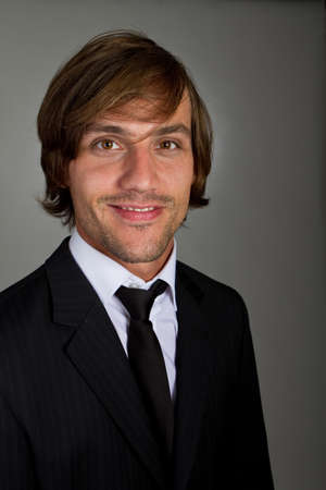 Young fresh confident businessman with longer hair over a greyish background. Stock Photo - 7619529