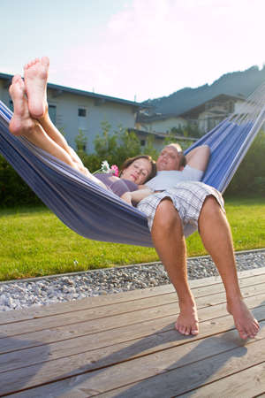 Young loving couple in a hammock in a summer setting. The woman is pregnant. photo