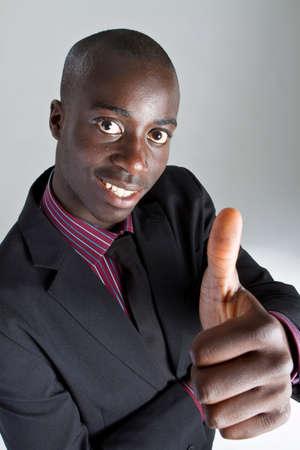actitud positiva: Joven empresario negro con traje sobre fondo gris. �l est� dando un pulgares arriba signo.