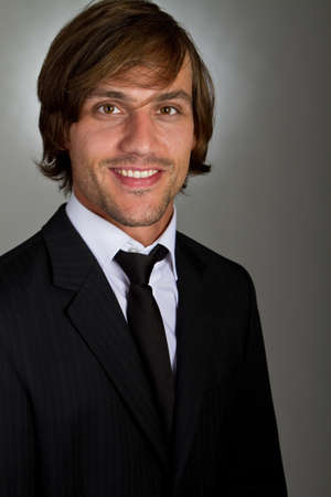 Young fresh confident businessman with longer hair over a greyish background. photo
