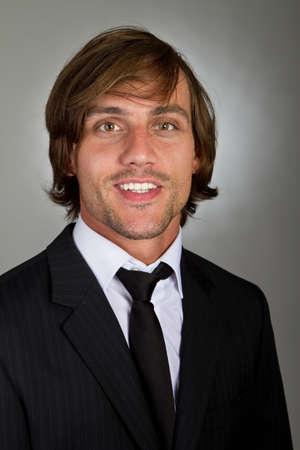 grigiastro: Giovane imprenditore fiducioso fresco con i capelli pi� sopra uno sfondo grigiastro.