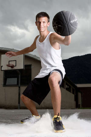 Young stylish teenage basketball player on the street with dark clouds over him. Stock Photo - 7718787