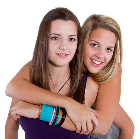 Two young girl friends smiling - isolated over white background.