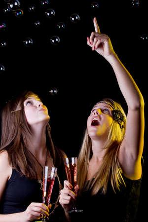 Jóvenes chicas adolescentes frescas de fiesta con las bebidas. Aislados sobre fondo negro.  Foto de archivo - 7825191
