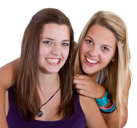 Two young girl friends smiling - isolated over white background. photo