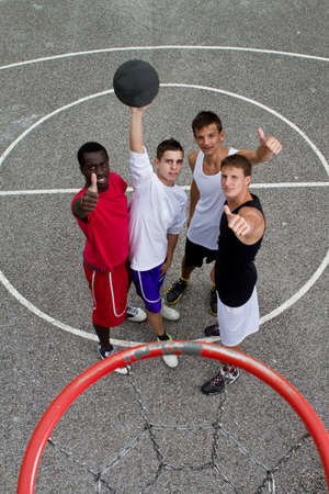 Young stylish group of teenage boys standing under a basketball hoop giving thumbs up sign. photo