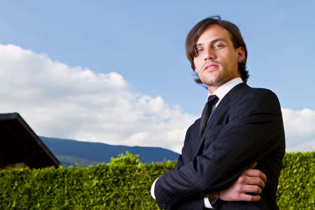 Young businessman in front of a house over blue sky.Young fresh model with longer hair. photo