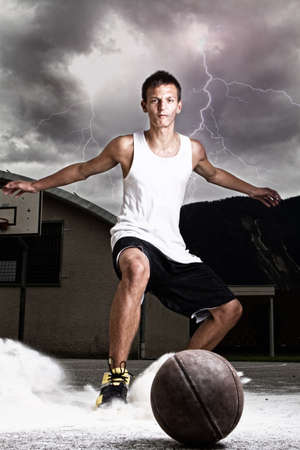 Young stylish teenage basketball player on the street with dark clouds over him. photo