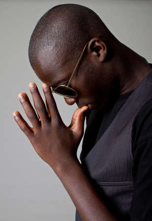 Young afro american teenager praying with sunglasses and a stylish suit.  photo