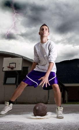 Young stylish teenage basketball player on the street with dark clouds over him. Stock Photo - 7947549