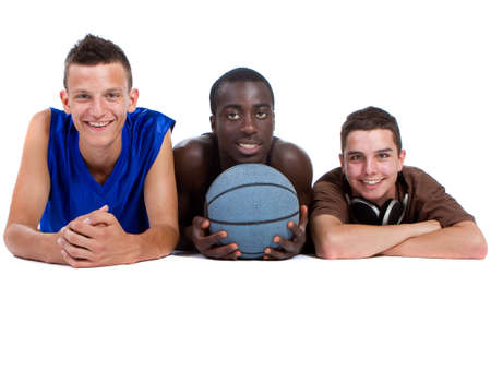 Young interracial group of happy sporty teenagers lying on the floor. Isolate over white. photo