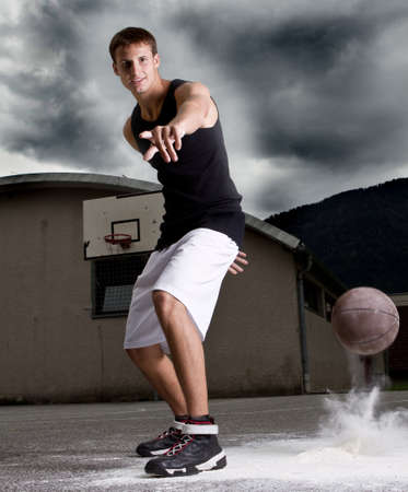 hand baskets: Young stylish teenage basketball player on the street with dark clouds over him. Stock Photo