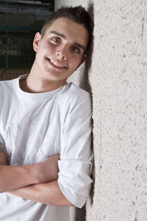 Young teenage boy leaning against a wall in anurban setting.  photo