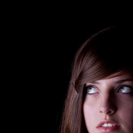 woman face close up: Teenage girl is looking in a corner isolated over black background.