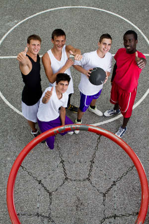 hoops: Young stylish group of teenage boys standing under a basketball hoop giving thumbs up sign.