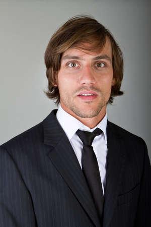 grigiastro: Giovane imprenditore fiducioso fresco con i capelli pi� sopra uno sfondo grigiastro.  Archivio Fotografico