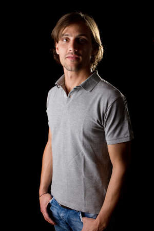 Young male model over black background with a grey shirt, with longer hair. photo