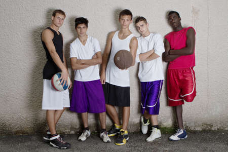 boy basketball: Young group of teenagers leaning against a wall. Stylish teens.