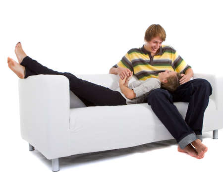 Young happy couple in love relaxing on a white couch enjoying their time together. photo