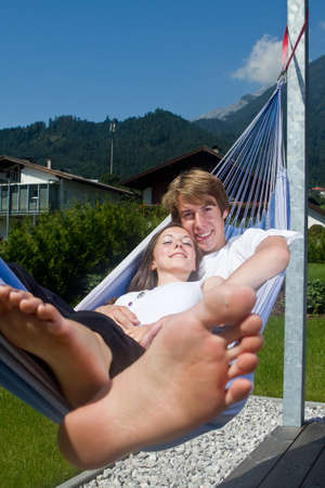 Young cute teenage couple in a hammock enjoying a sunny afternoon. photo