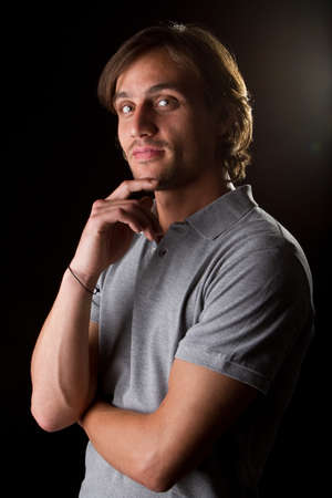 Young male model over black background with a grey shirt, with longer hair. Stock Photo