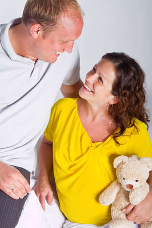 Young couple on a couch. The woman is pregnant and they seem to be in love. photo