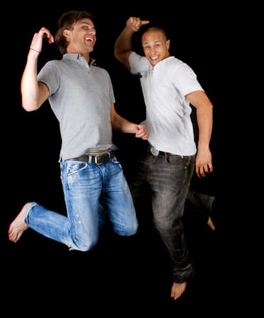 Two young successfull men jumping in joy. Fresh multiracial models. photo