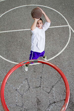 Young basketball player on the street going  to the hoop. Great angle from above. photo
