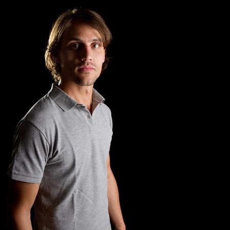 young male model: Joven modelo masculino sobre fondo negro con una camisa gris, con el pelo m�s largo.