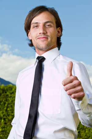 Young businessman with thumb up sign over a blue sky in the background. photo
