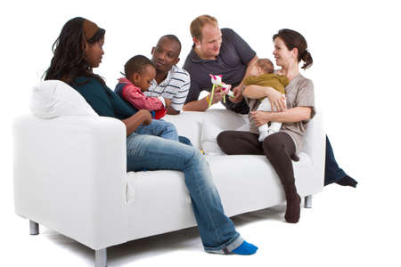 Young befriended multiracial families sitting on the couch and playing with their kids. Stock Photo - 8158109