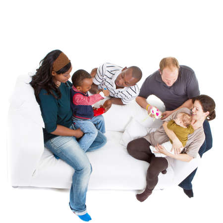 Young befriended multiracial families sitting on the couch and playing with their kids. Stock Photo - 8158123