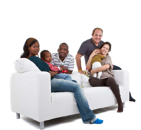 multiracial groups: Young befriended multiracial families sitting on the couch and playing with their kids. Stock Photo