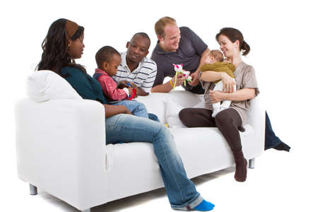 Young befriended multiracial families sitting on the couch and playing with their kids. Stock Photo - 8158213