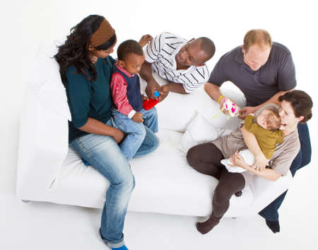 Young befriended multiracial families sitting on the couch and playing with their kids. Stock Photo - 8158215