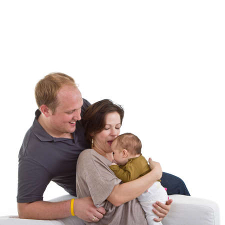 Young happy couple on a couch with their baby over white background. Stock Photo - 8158216