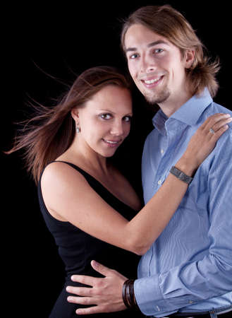 Young cute couple with long hair over black background. photo