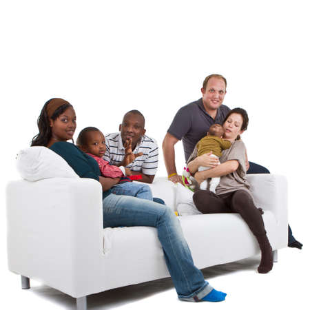 Young befriended multiracial families sitting on the couch and playing with their kids. photo