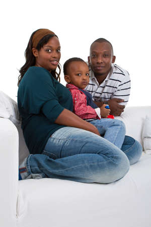 Young afro american family of three on a couch over a white background. Stock Photo - 8271943