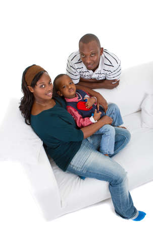 Young afro american family of three on a couch over a white background.