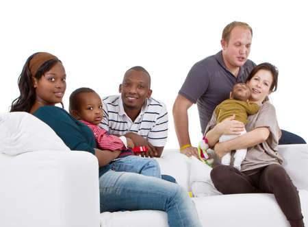 Young befriended multiracial families sitting on the couch and playing with their kids. Stock Photo