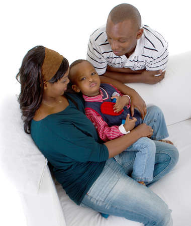 Young afro american family of three on a couch over a white background. photo