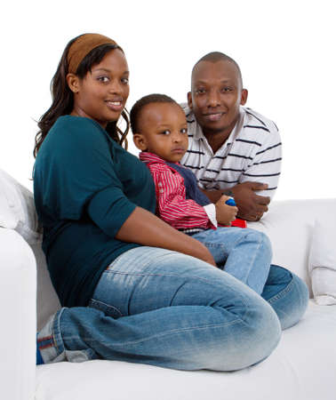 diverse: Young afro american family of three on a couch over a white background.