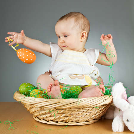 small basket: Young babay girl sitting and playing with easter egg. Very cute baby.